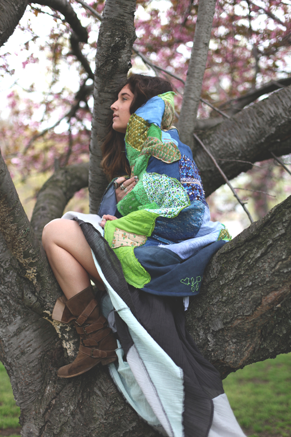 girl in tree wrapped in blanket