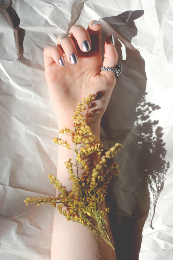 Hand, silver nail polish, yellow flower