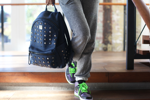 Sweatpants, sneakers, studded backpack