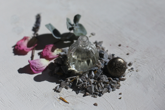 Open perfume bottle, dried plants, pebbles