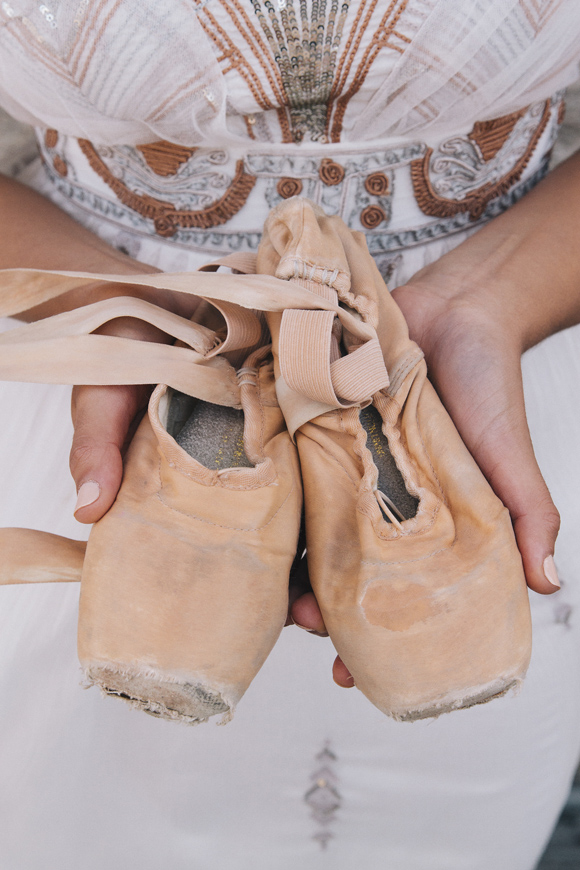 holding ballet shoes